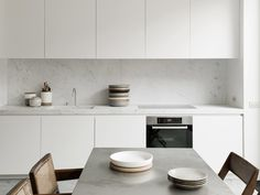 Kitchen: matt white handleless cabinets, marble splashback and benchtop, concrete dining table, wooden chairs