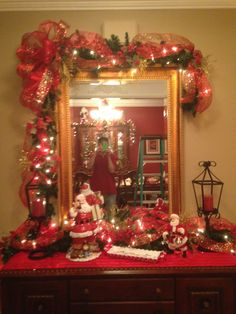 Christmas Entry-way mirror adorned with Christmas garland swag  using multi-ribbon bow and ribbon weaved throughout garland. Also used multiple ornaments and gold shiny filler branches.  Entry table also adorned with greenery and ribbons with Santa and a wrought iron candle holder. (Hamptons- November 2015). Designer Sidney Nicholson. Southern Traditions--Booneville, MS --662-728-1876