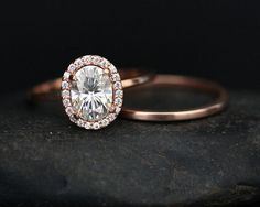This Stunning delicate and feminine 14k Gold Single Halo Ring Features a flawless Forever Classic Moissanite measuring 8x6mm and surrounded with Natural Diamonds Halo. The Ring has a Plain Gold Band without Diamonds. The Ring comes a Matching Plain Gold Wedding Band worn together. If you would like any other Gemstone set in this Ring, please convo me. Please read my CUSTOM ORDER Section for further information. Details: Solid 14k Rose Gold(shown in picture) Charles & Colvard Forever Class...