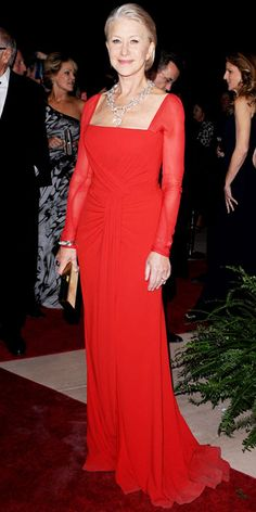 Helen Mirren wearing a bright Escada gown, statement jewels and a bronze Tory Burch box clutch.