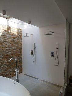 Badkamer in een souterrain met dubbele douche en wanden van stucwerk. Licht komt door een dakraam uit de patio.