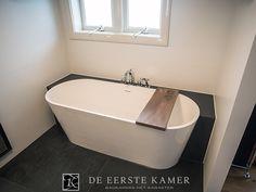 (De Eerste Kamer) Het vrijstaand bad is aan de achterzijde ingebouwd. Het houten planchet boven het bad kan gebruikt worden voor het nuttigen van een drankje of voor het gebruik van een tablet. Meer inspiratie vindt u op www.eerstekamerbadkamers.nl