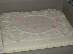 Covered in white buttercream with pale pink gumpaste flowers and...