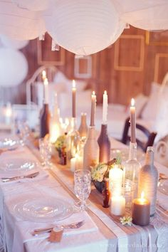 simple idea for a centerpiece using covered wine bottles and colored candlesticks