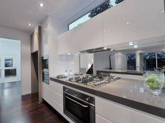 warmed up kitchen dark floorboards white cupboards grey bench