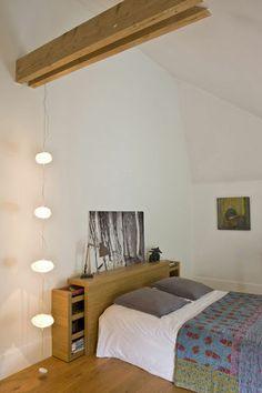Une tête de lit avec tiroirs et tablettes de rangement