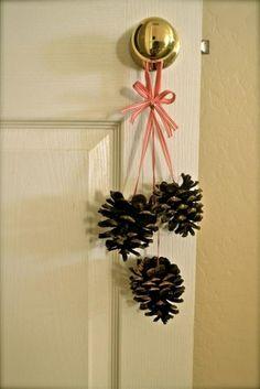 Toute simple et vraiment pas chère : une idée de décoration de Noël à fabriquer soi-même avec des pommes de pin et du ruban. On aime l'idée de l'accrocher aux poignées des portes un peu partout dans la maison !