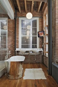 rustic industrial bathroom; silver tub, exposed piping, exposed brick walls