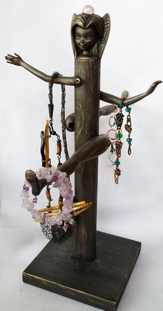 """Jewelry display, part of Small Arms collection - using Barbie arms and legs. Black with touches of gold, about 15"""" h x 14"""" w. Gilding The Lily by Candace Eck"""