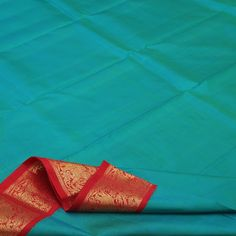 Not a ripple disrupts the placid and serene azure blue of this #Sarangi #silk sari. The vermillion border provides a vivacious contrast. Woven with elephant, peacock, horse and creeper motifs in gold, the border lends the sari an air of opulence. The fiery red pallu is a flame with gold checks and traditional motifs. Like most of our Kanjivarams, this too comes attached with a blouse fabric: plain red blouse with running border. For such beautiful blues, visit Sarangi. Code 180126335.