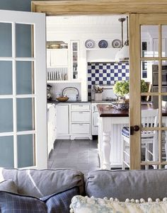 french doors leading into a blue and white kitchen.  so calm-looking