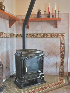The Arts & Crafts inspired Wood Stove Surround is made up of a number of sizes of hand-crafted stoneware tile accented by a hand-painted, glazed and f… Wood Stove Surround, Wood Stove Hearth, Wood Burner, Wood Mantle, Wood Burning Stove Corner, Corner Stove, Stove Fireplace, Fireplace Hearth, Fireplace Ideas