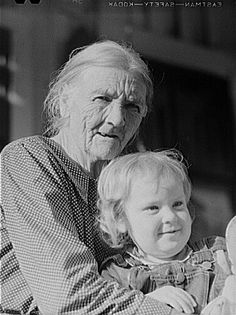 Mountain woman and grandchild sitting on the porch of their home up Frozen Creek, Breathitt County, Kentucky 8c13883u