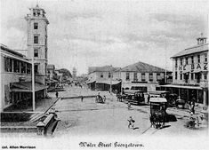 "Downtown Georgetown, Guyana, in the 1890s. View is south from Water and Church Streets . The tower on the left belonged to the Royal Agricultural Society. The tower in the distance, at the other end of Water Street, is at Stabroek Market. The horsetrams on the right are labeled ""Vlissingen"" and ""Belair"" [col. AM]:"