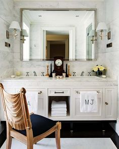 ECLECchic Large chrome frame mirror, marble vanity surface and walls, monogrammed towels hung on drawers*