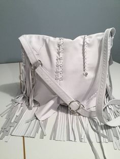 "Classy white crossbody bag has a very detail front flap. One of a kind.  Fringe on both sides and bottom.  Measures 12""w x 11.5""h x 3""d.  Inside has a grey polka dot lining and 5 pockets.  Closes with a magnet under flap.  Back outside zipper pocket."