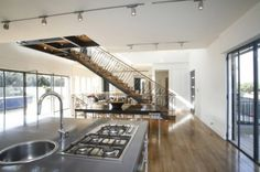 First and foremost, stairs that lands in the middle of a space become an object. In this case all of the pieces — treads, risers, stringers, guardrails — take on a strong presence as the stairway separates the kitchen from the living area.