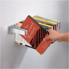 Cool idea. Fly-brary-Book-Shelf. Satina Turner's powder-coated metal wall mounted bookshelf allows books to hang on metal strips which in turn create the surface of the shelf...very clever!
