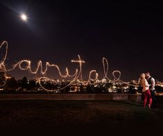 "Among the city lights, ""fairytale"" is written with sparklers for a romantic engagement photograph."