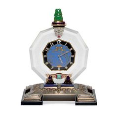 AN ART DECO MULTI-GEM AND DIAMOND DESK CLOCK, BY THE GROGAN COMPANY  With nickel-finished lever movement, 11 jewels, 3 adjustments, the nine-sided polygon-shaped blue and black enamel dial, depicting two gold angels, with rose-cut diamond Arabic numerals and hands, within a rock crystal frame, topped by carved jade lovebirds sitting on a rose-cut diamond and cabochon ruby plaque, the base set with lapis lazuli, silver, 18k gold and onyx, (with one winding key), circa 1930