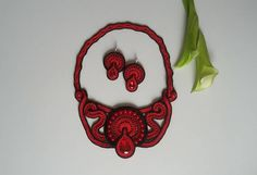 A statement bib necklace made in soutache embroidery technique in red and black with earrings. This stunning pieces of jewelry are made of soutache braid, beads, crystals and glass beads. Necklace fits comfortably around neck, the centerpiece is about 6 3/4 inches (17cm) from end to end and 3 1/4 inches (8 cm) at its widest in the center. Length of chain (measured form end of center piece) – 12 1/2 inches (32 cm) which made circle of 18 ½ inches ( 47 cm) around neck. It has hid...