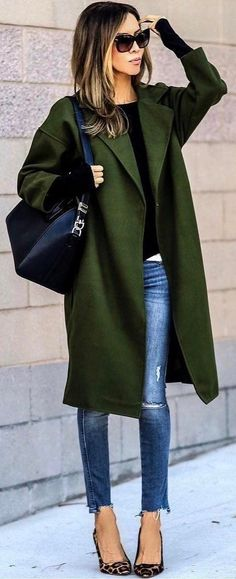 Hunter green coat over black sweater with blue jeans.