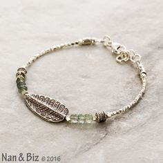 Our new Hill Tribe silver bracelet combines two contemporary favorites — faceted green moss aquamarine gemstones and handmade fine silver beads, like the large, 12 x 25mm tribal leaf, ornate accent beads, and 1.75mm (and larger) silver nuggets. The tribal leaf is especially breathtaking, made of two hand-cut, bench-made leaves soldered together, meticulously decorated on both sides and lightly oxidized to display the gorgeous tribal design. The bracelet is closed by a sturdy, US-sourced…