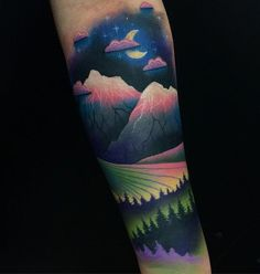 Another colorful mountain tattoo. The hues are a mixture of dark palettes and pastel ones which gives it a smooth and soothing effect.