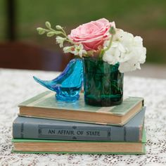 Low centerpieces featured glass knickknacks and small glasses filled with pink roses on top of vintage books.