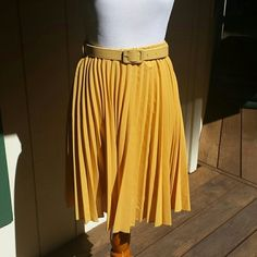 """Final Reduction Pleated Chiffon Skirt This adorable mustard colored chiffon skirt will look great in the fall and winter with boots or with sandals or pumps in the spring and summer. The narrow and flat tonal waist belt accents the silhouette and adds some elegance. It is satin lined, 100% polyester and machine washable. In great condition, worn three times.  Measures 20"""" in length. Chicwish Skirts"""