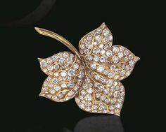 A DIAMOND FOLIATE BROOCH, BY VAN CLEEF & ARPELS  The circular-cut diamond sculpted leaf, enhanced by polished gold veining and stem, mounted in 18k gold, circa 1966 Signed Van Cleef & Arpels, NY, no. 36960-1