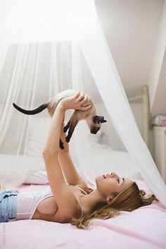 Young woman with siamese cat by Jovana Rikalo for Stocksy United