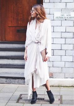 Maja Weyhe of Maja Wyh wears a white knotted maxi dress, black ankle boots, a neutral clutch, and round sunglasses