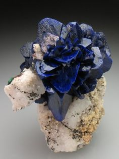 A gorgeous 'rose' formed of Azurite blades, on matrix! The Azurite is bright to deep blue and very lustrous, and well crystallised. Azurite roses from Morocco are normally found as floater specimens, and it is rare to see a rose of this quality on matrix. Morocco » Oumjrane Mine