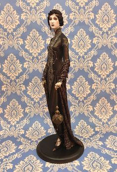 Shantay  Alexandra Koukinova doll Biscuit porcelain.  Beaded threads of four colors. The central strip on a dress is embroidered by silver, bronze and brass threads and decorated by strasses and beads. Shoes are made of natural suede and laces. The hair dress «undulation» is executed from natural silk, gold threads and decorated by a feather of cassowary. LE 15, 60cm www.alexandra.ru