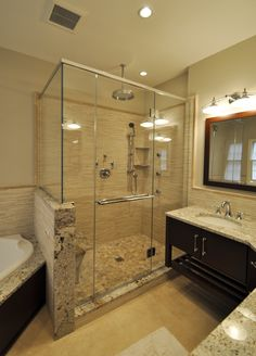 Stand up shower with rain head, body sprays, bench seat, shower wand, frameless shower doors, floating corner double vanity, and corner air tub.