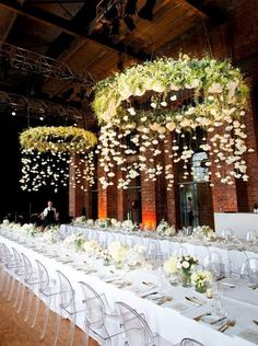 Hanging features can be suspended above guest or bridal tables, drinks or dessert tables, dance floors, and from ceilings of mandaps or any event space and even from trees if your event is outdoors - modern Indian wedding - perspex chairs - long tables - floral wedding decor - hanging rings - white flowers and greenery #thecrimsonbride