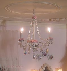 The chandelier. I made it from glass beads, Swarovski crystals, wire, q-tips, polymer clay sculpted roses, jewelry findings and of course three wired bulbs. I love the result.