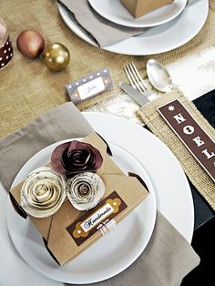 These place settings for a Christmas party feature handmade favor boxes.