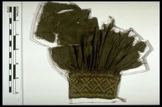 A fragment of a garment, probably part of a sleeve, with gathered cuff and embroidery (smocking). Dark brown twill weave wool, fragmentary, with fraying edges. Obne edge with fine pleats held in place with gathering stitches and with smocked embroidery in a pale brown thread 1501-1599, ID no. A26865, in store
