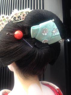 芸妓さんと舞妓さんのブログ (HAIRSTYLES OF MAIKO: OFUKU)  Tegara is that piece of fabric in the middle of the bun. It can be red, pink or even blue or green. In some districts, color of tegara changes as a maiko gets older. So right after changing her hairstyle from wareshinobu to ofuku, she wears red tegara, then pink and before next stage of her career (erikae) - blue one.