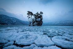 Au Japon, l'aube se lève à peine sur le lac Towada, un lac de cratère de 327 m de profondeur, complètement gelé en hiver - National Geographic France