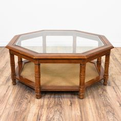 This octagon coffee table is featured in a solid wood with a glossy cherry finish. This large coffee table has an octagon glass inset table top, carved square legs and a woven cane bottom tier. Perfect for holding drinks and snacks! #bohemian #tables #coffeetable #sandiegovintage #vintagefurniture