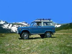 Nice Blue Bronco with a rack and mountains in the background.