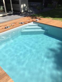 Voorbeeld van een hoektrap in een zwembad met een grijze gewapende folie. De afwerkrand is gemaakt van hardhout.