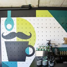 The studio's design covers the whole of the opposite wall, beginning with Bar Testoni's brand character, a monocled and moustachioed gent made of a teaspoon and a coffee cup...