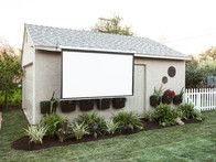 Even with the movie screen pulled down, a planting bed beautifully frames the screen. When designing an outdoor space, think how you will use it, and plan for ways to inject plants and flowers into even the most utilitarian spaces.