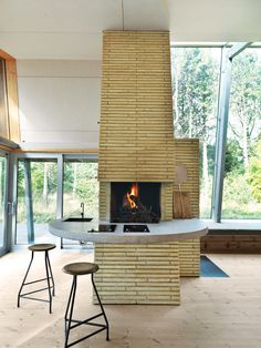 The summer home features an indoor fireplace with a countertop that wraps around to the kitchen area.