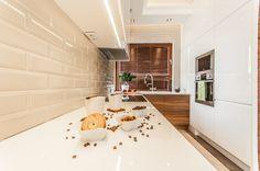 Biała kuchnia z elementami cegły i drewna.