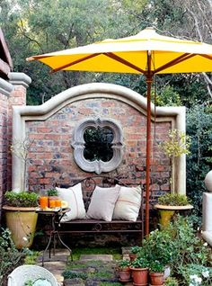 Accents for small patio: yellow umbrella, stunning brick feature wall with quatrefoil window